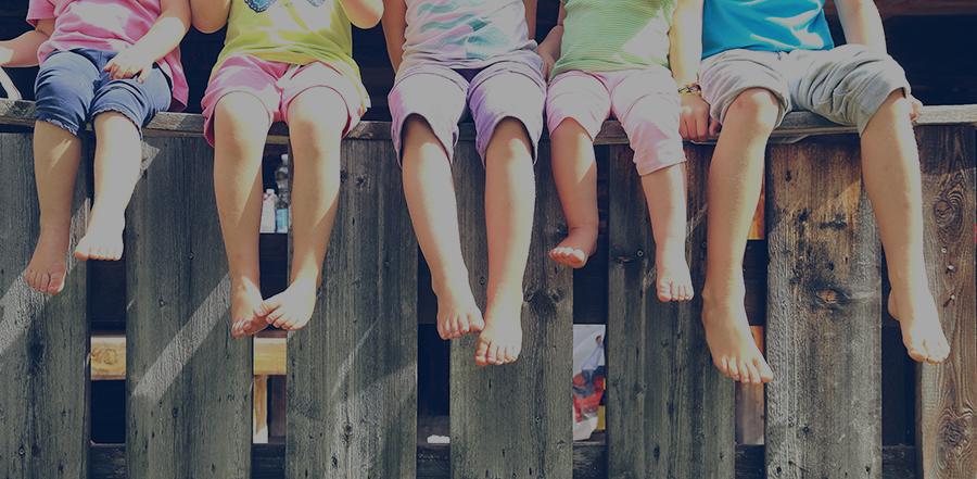 Kinder auf einem Zaun