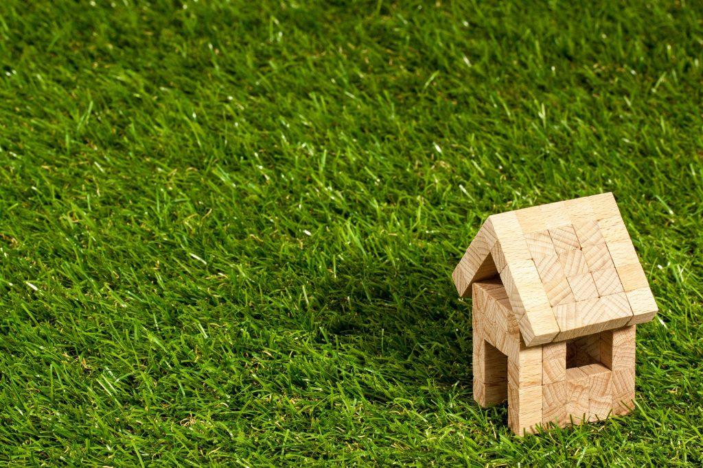Ein kleines Holzhaus auf grünem Rasen